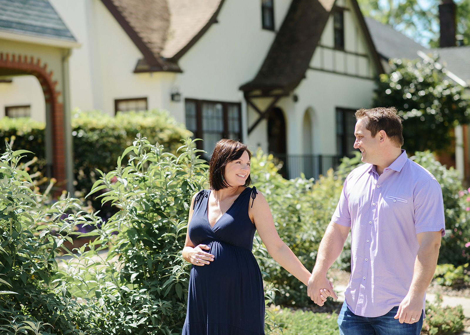 Pregnant couple holding hands and smiling in front of their home