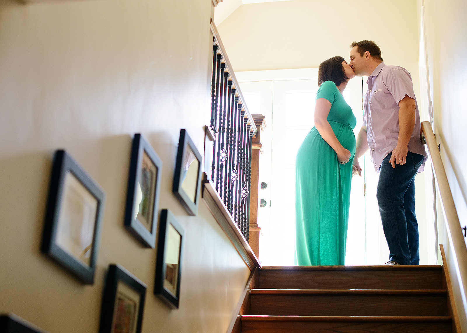 Pregnant couple on top of stairs kissing