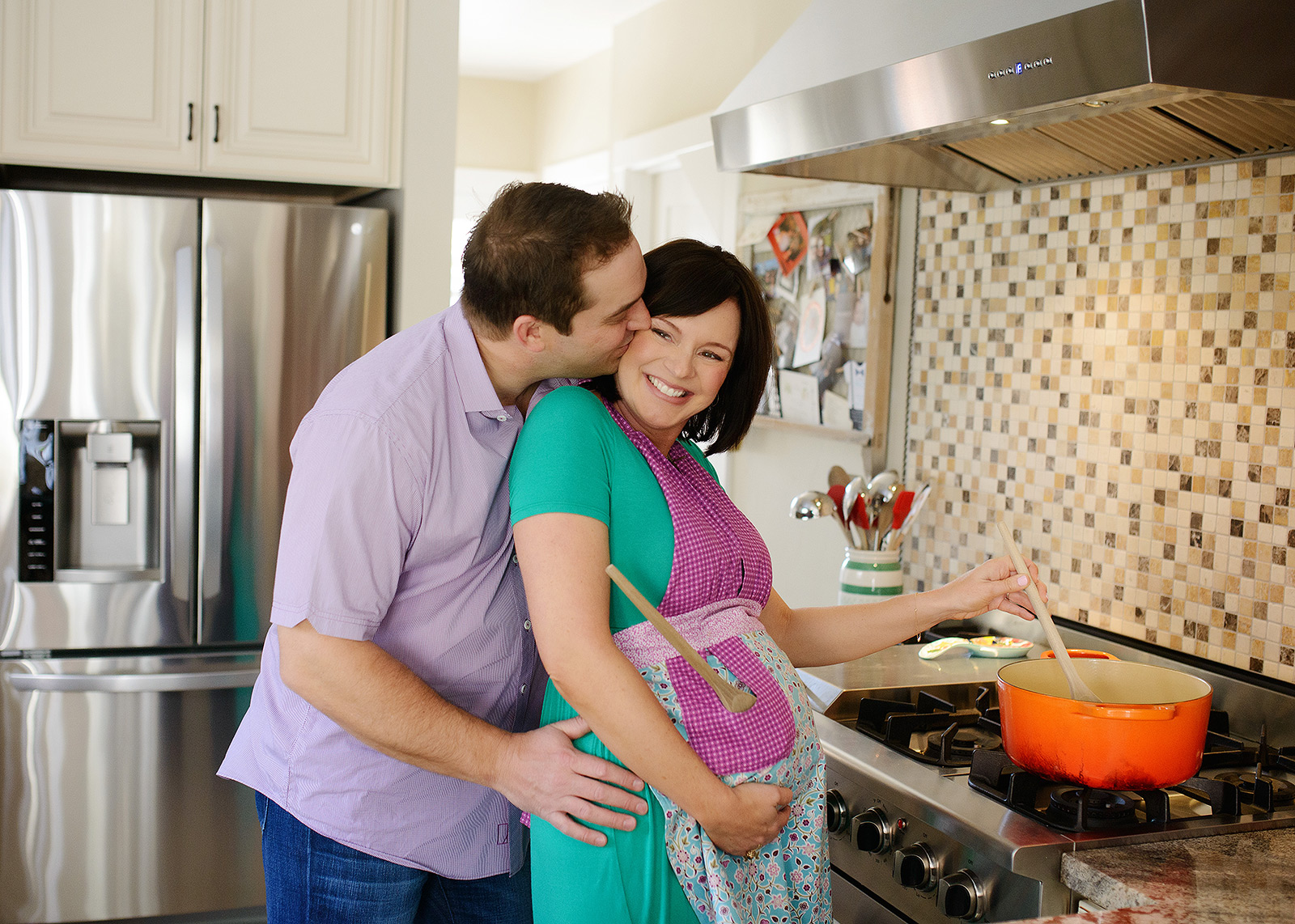 Pregnant woman wearing apron and cooking in kitchen as husband kisses her