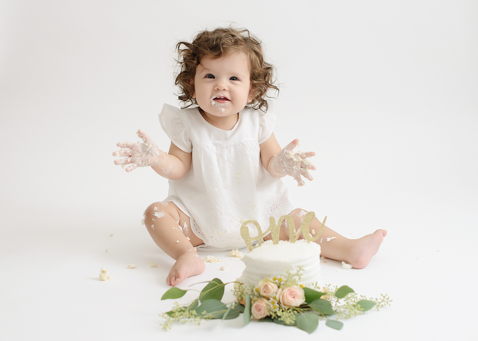 One Year Old Baby Girl Smashing Cake with Flowers