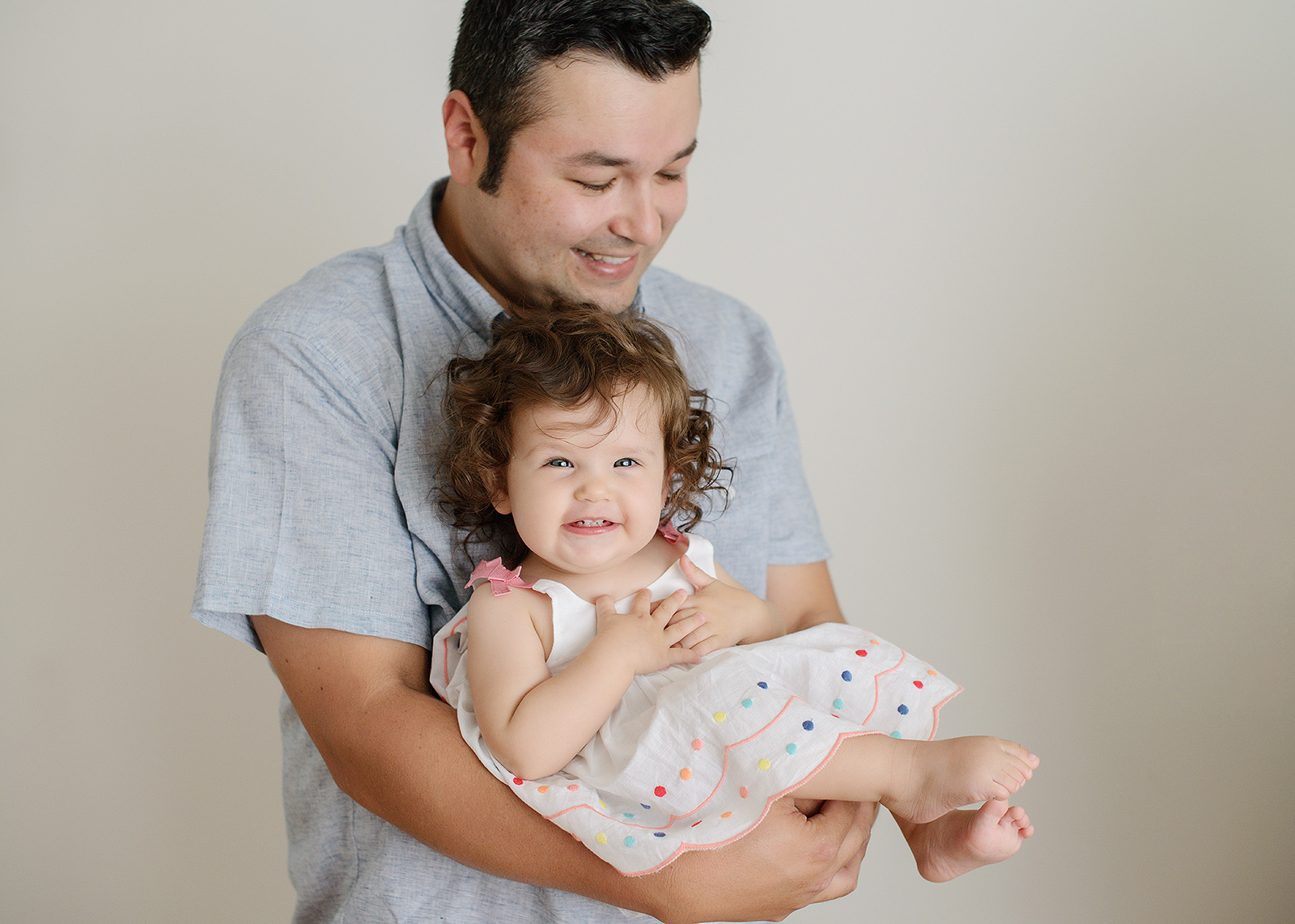 Dad Holding Baby Girl Who is Smiling Against White Background