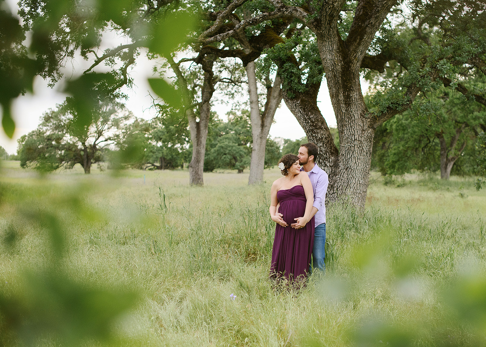 Pregnant couple hugging under a tree in Folsom