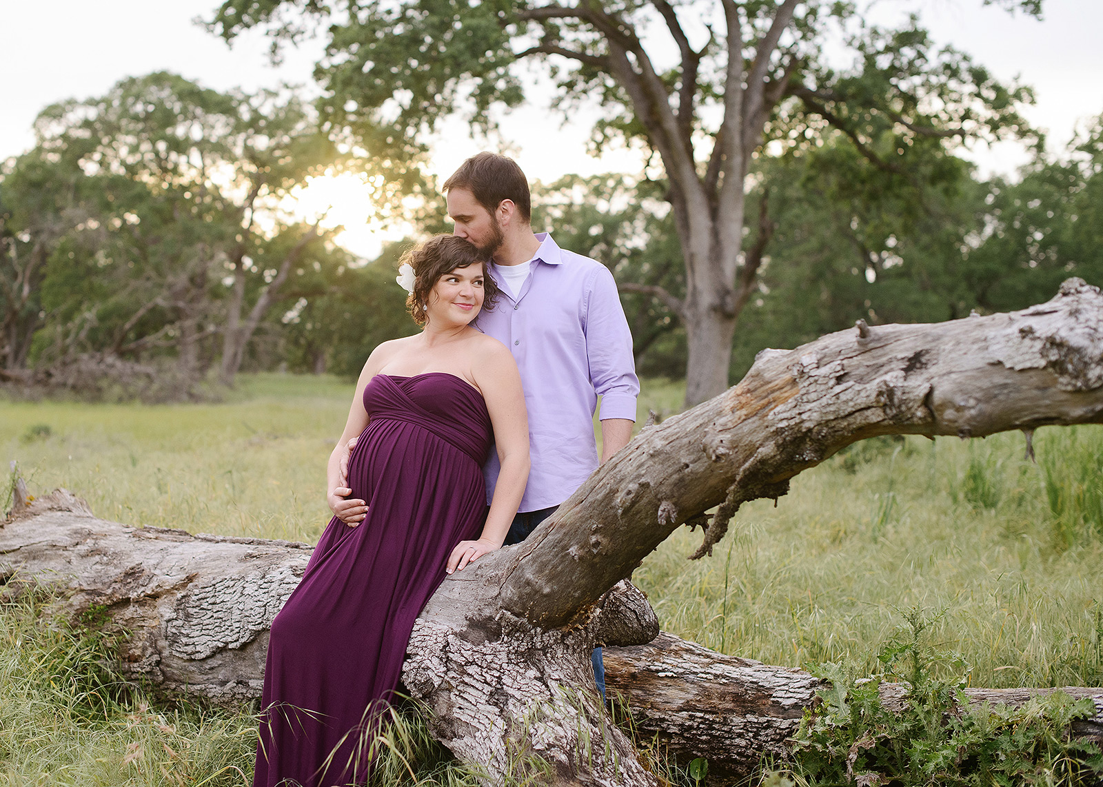 Pregnant couple sitting on fallen tree log outdoors in Folsom