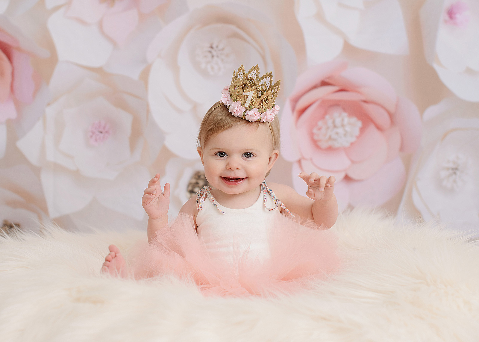 One year old girl wearing pink tutu and crown against floral backdrop in Sacramento portrait studio