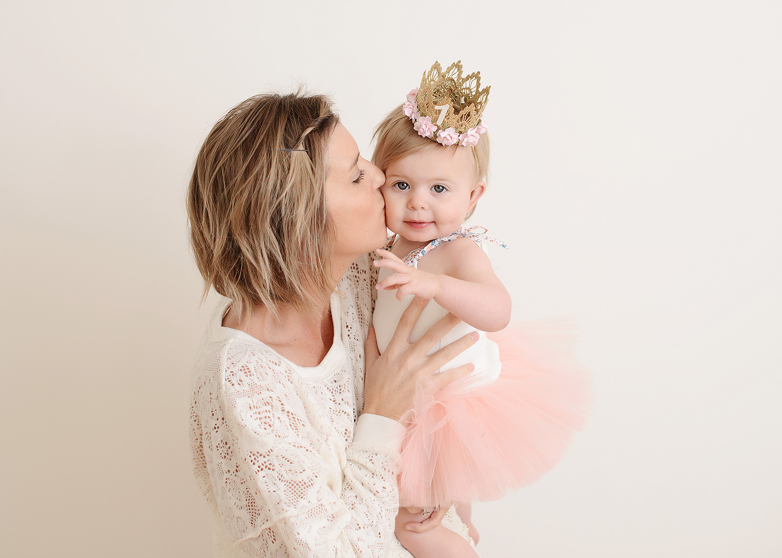 Mom kissing baby girl and celebrating one year