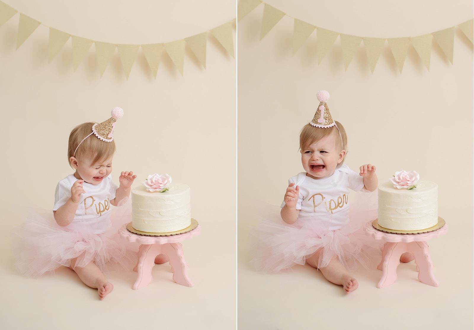 Baby girl in pink tutu smashing cake and crying