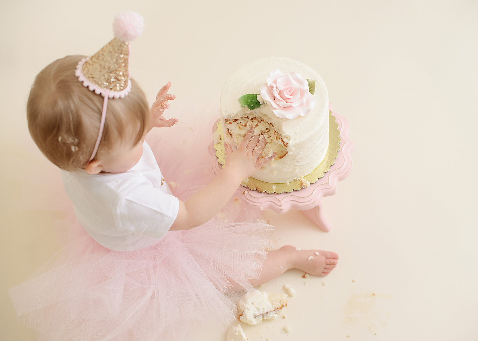Baby girl in pink tutu smashing cake from top in Sacramento studio