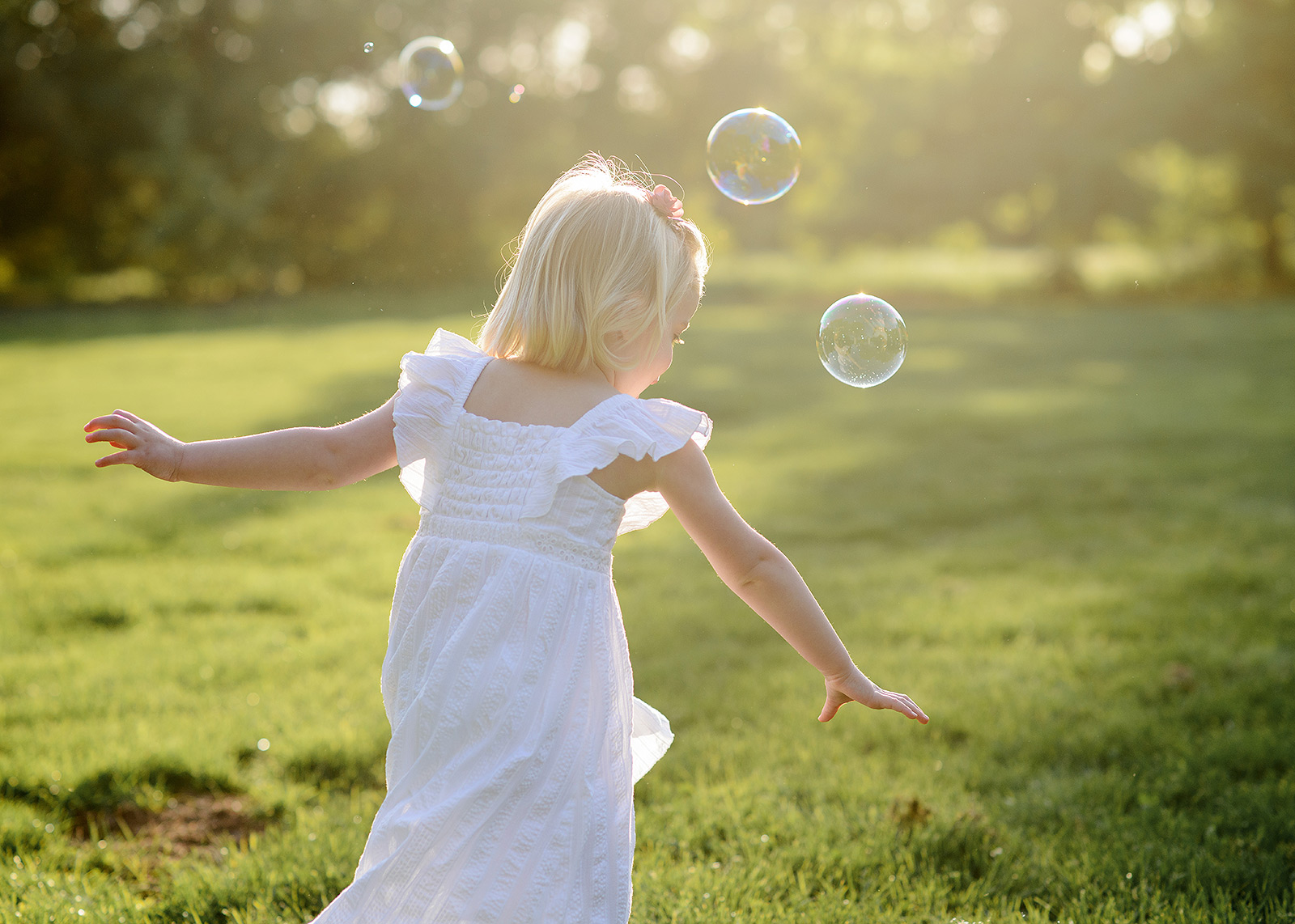 Daughter in white dress chasing after bubbles during Spring sunset