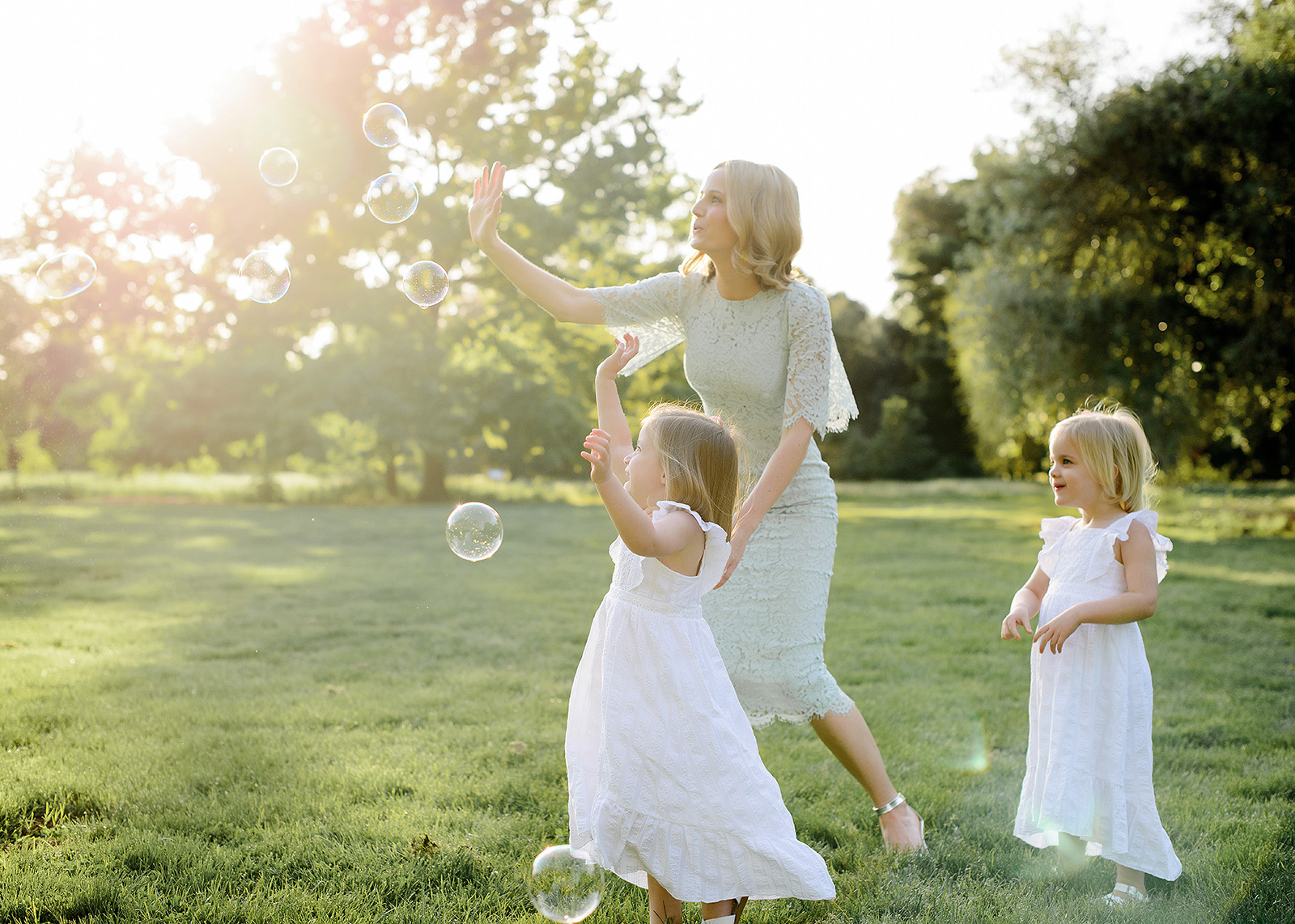 Mom and daughters blowing bubbles outdoors in Sacramento