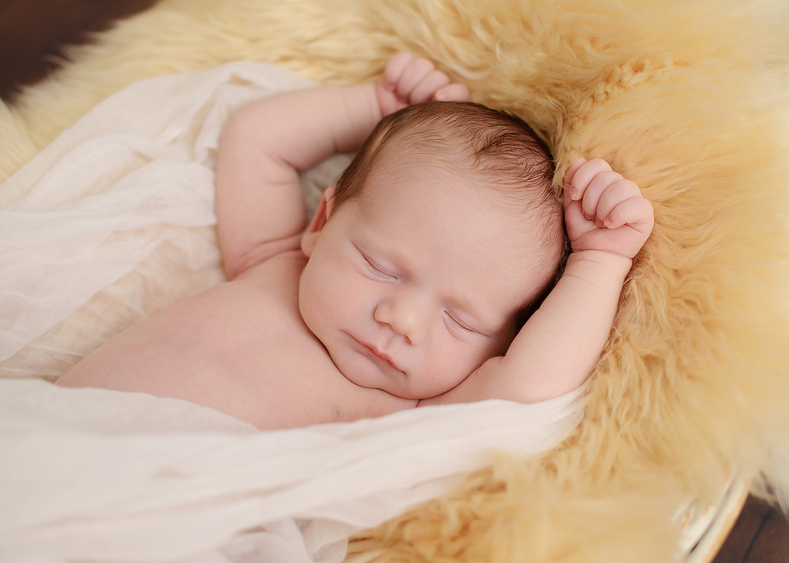 Newborn baby girl sleeping with arms up in muslin cloth and fur throw