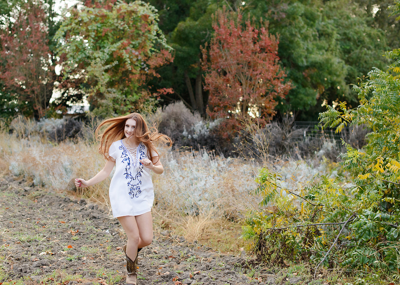 Senior Girl Running in Cowboy Boots and Tunic in Sacramento Outdoor Field Foliage