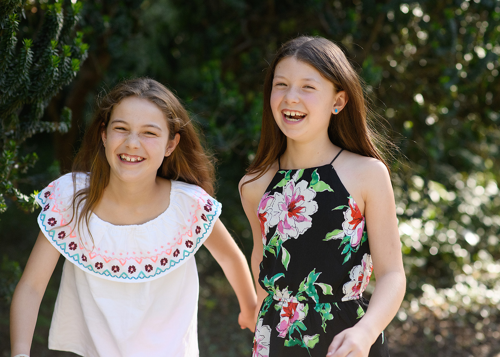 Sisters wearing floral print outdoors with trees in background