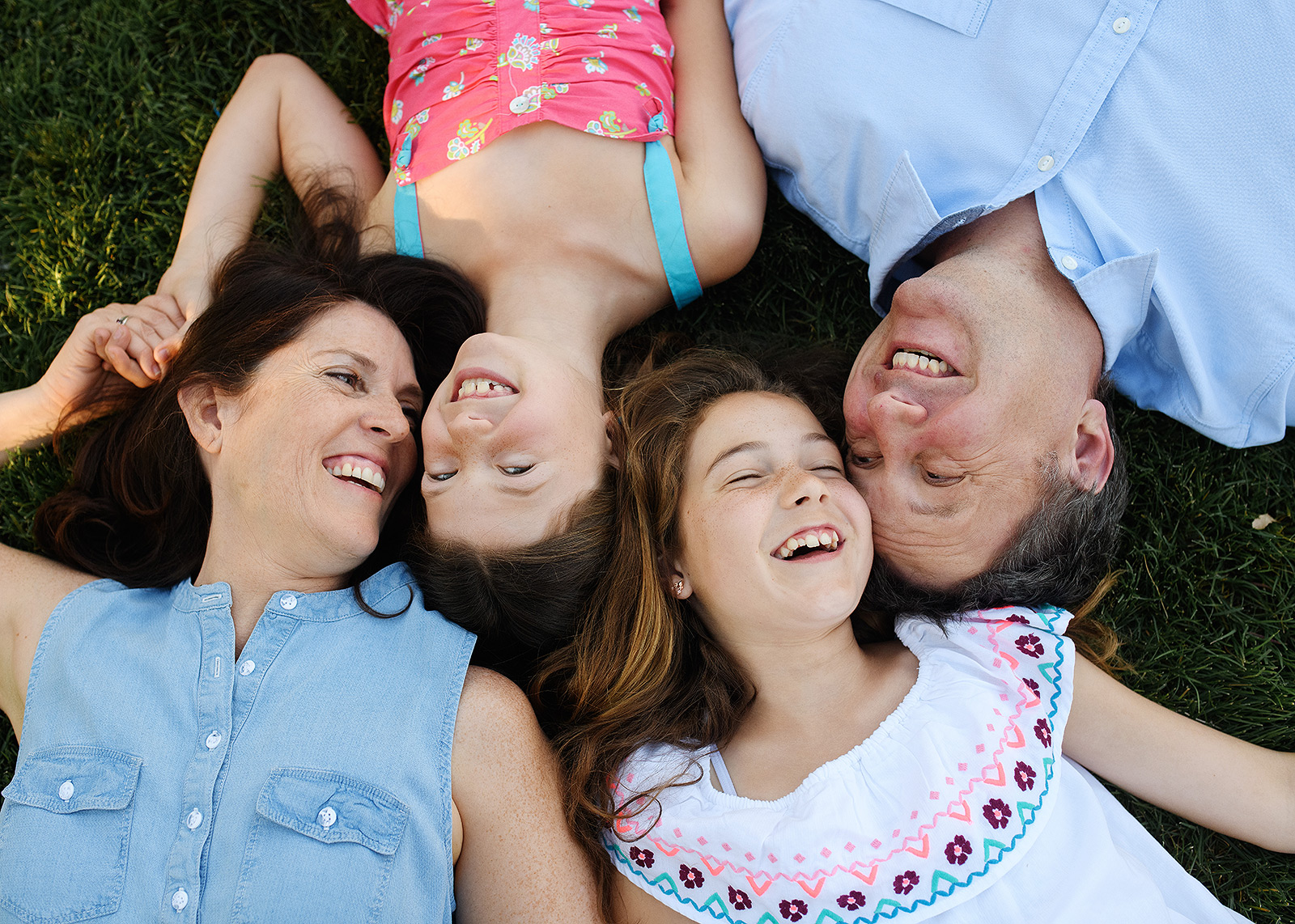 Family smiling and lying on grass outside