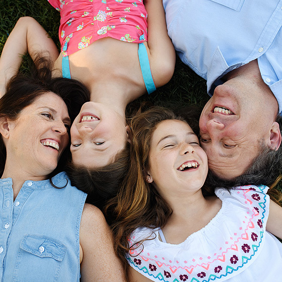 Smiling family with two sisters lying on the grass in Sacramento