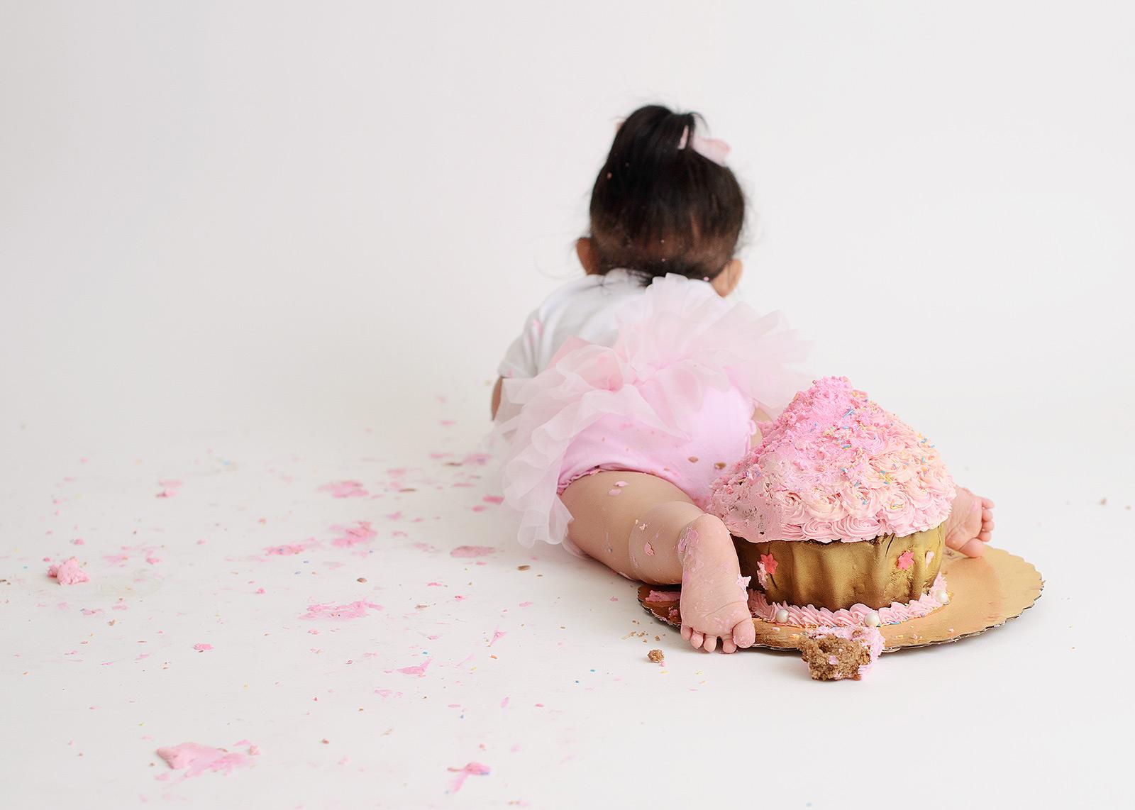 Baby girl in tutu crawling away from pink cake smash