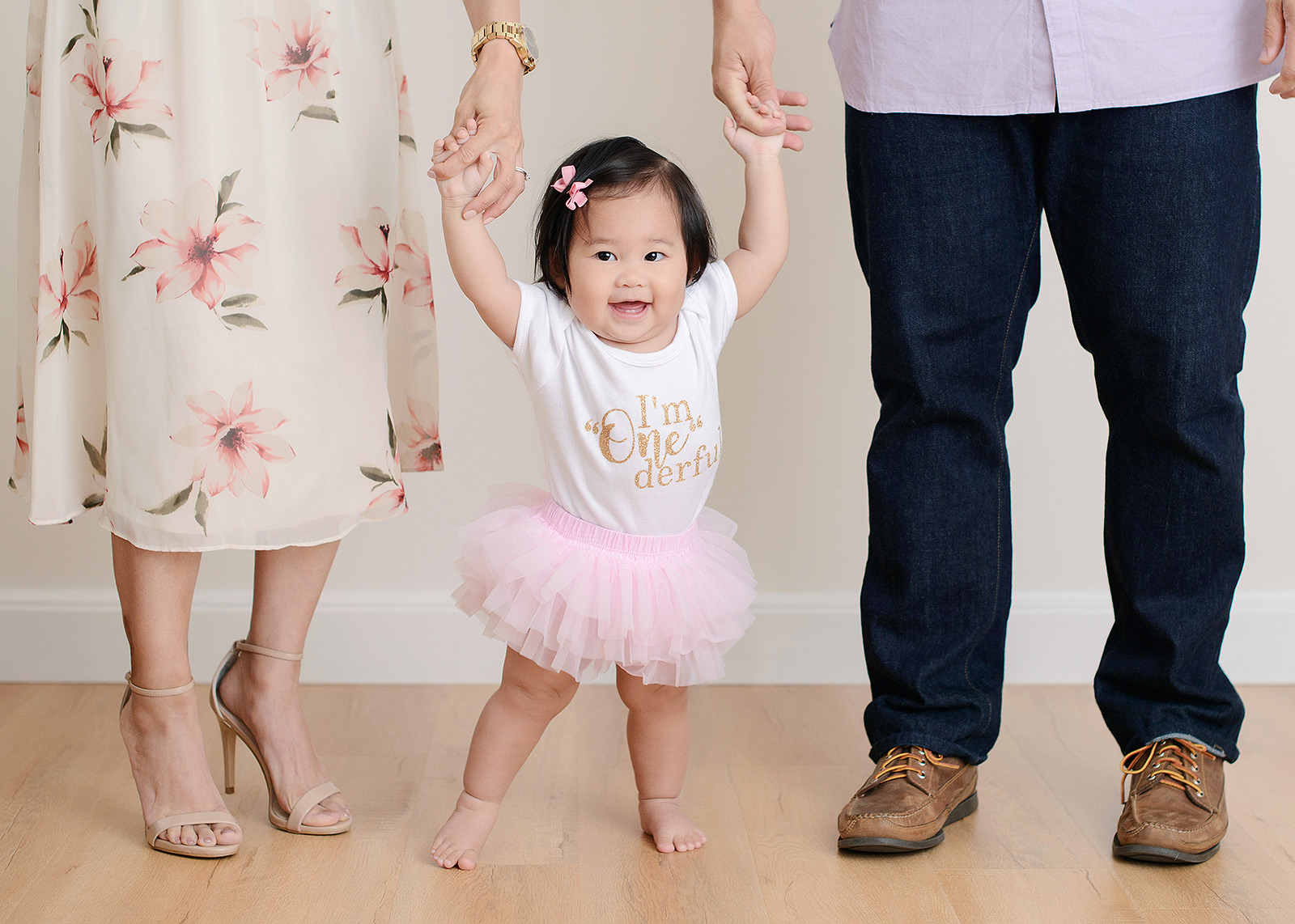 Baby girl in pink tutu being assisted by mom and dad to stand