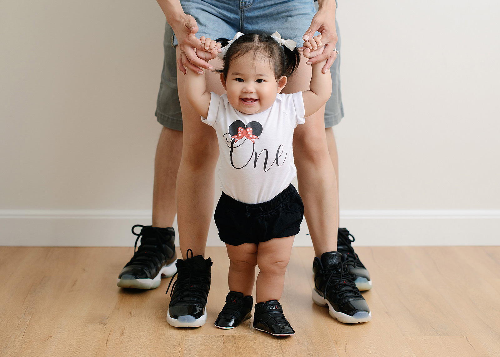 Baby girl standing up with close up of family wearing Air Jordans