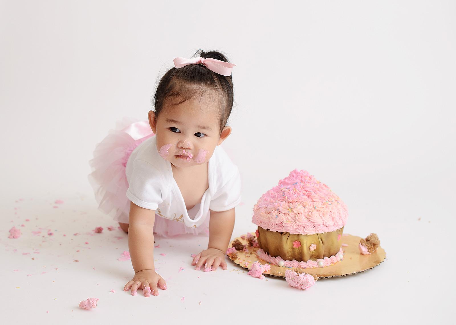Baby girl wearing tutu crawling towards pink rosette cake smash