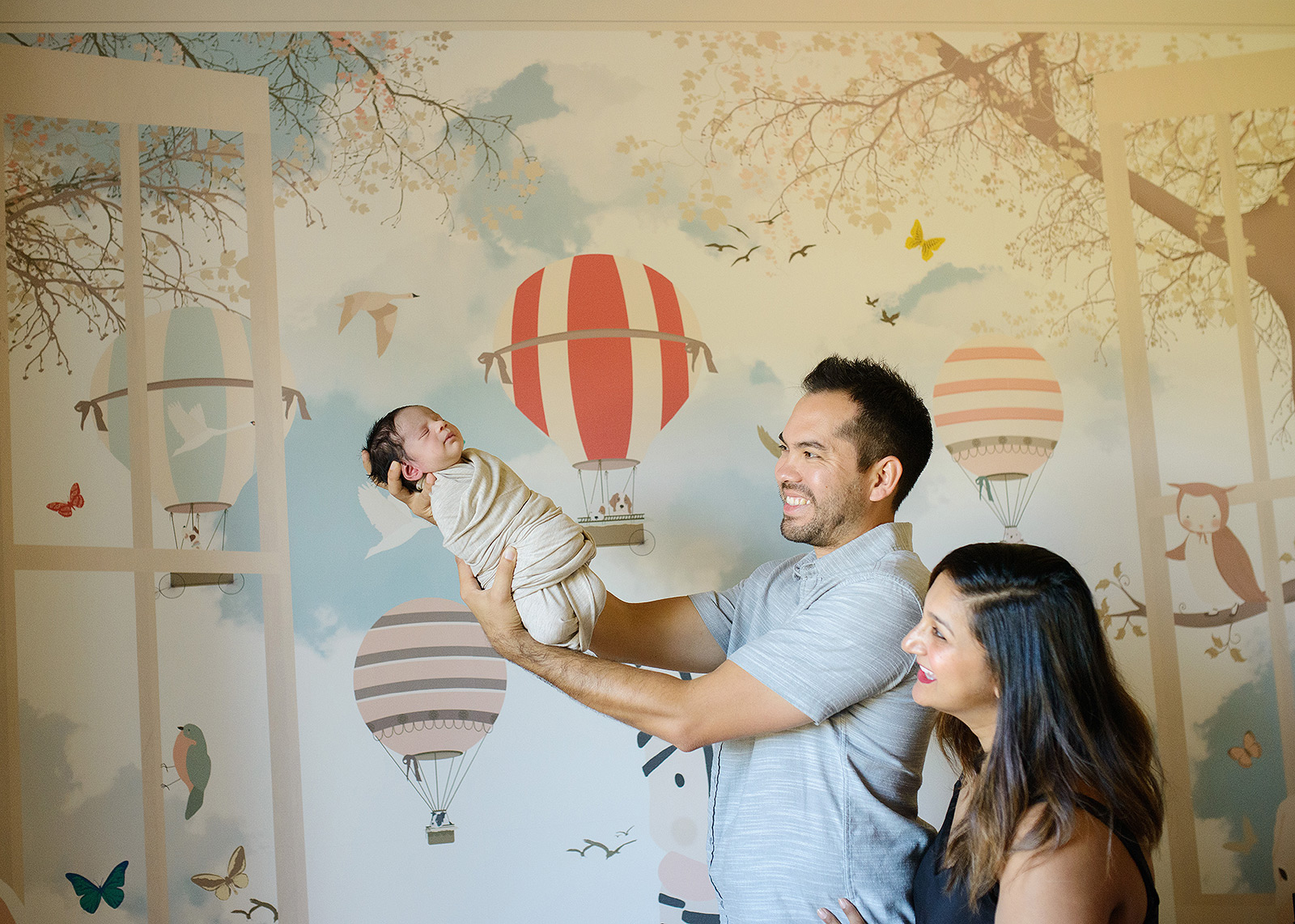 Dad holding newborn baby up against hot air balloon wallpaper in nursery