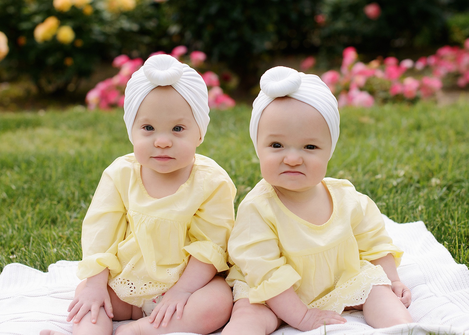 Twin girls wearing yellow and white turban sitting up on grass at Sacramento State Capitol