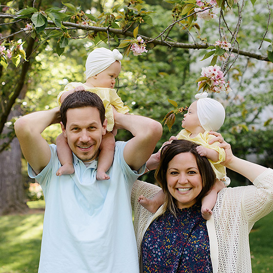 Family photo with twins on mom and dad's shoulders underneath cherry blossom tree
