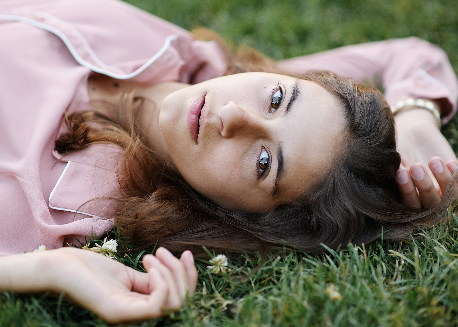 Senior girl lying on grass wearing dusty rose top in Sacramento