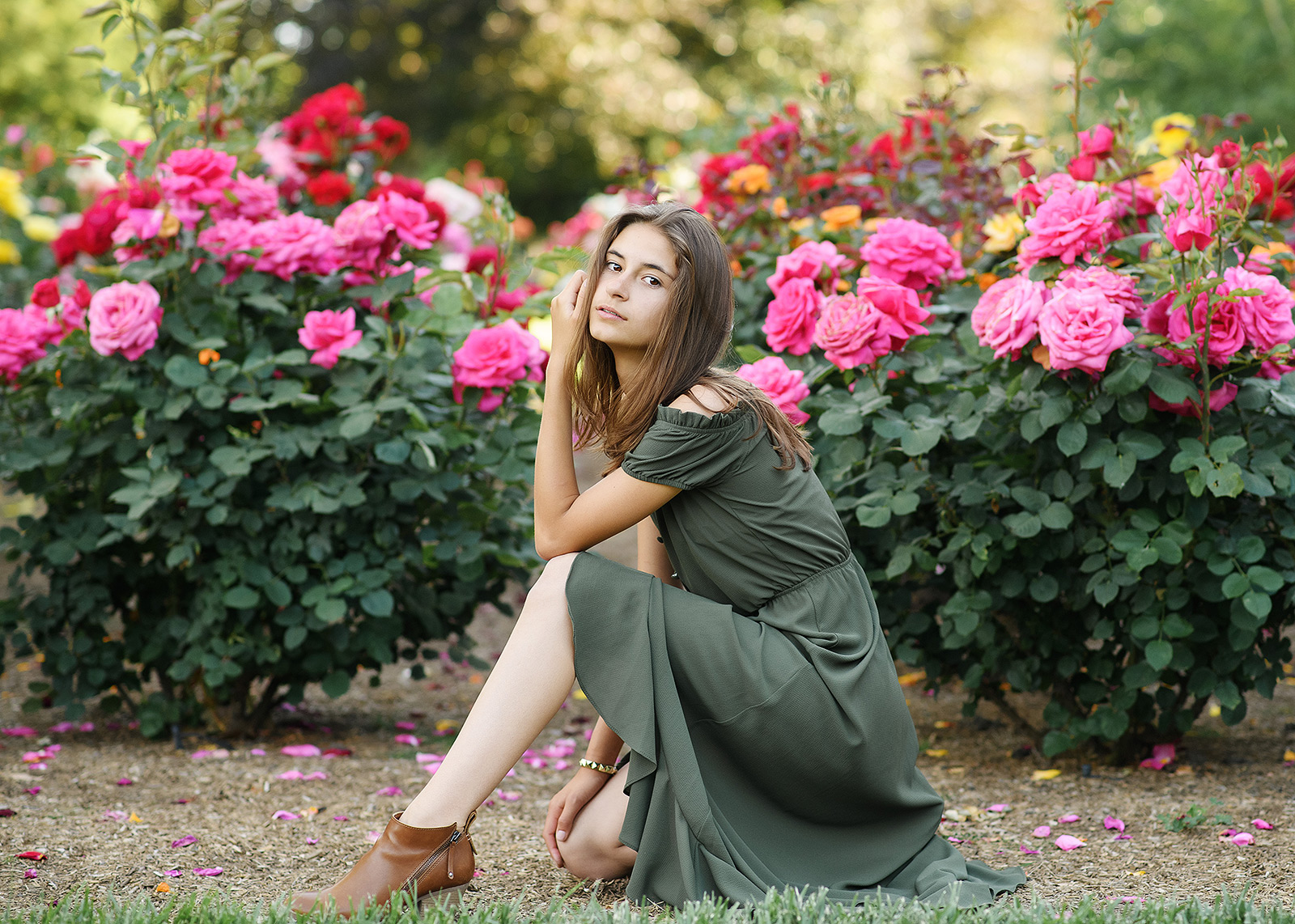 Senior girl posing by pink flowers outdoors in Sacramento State Capitol