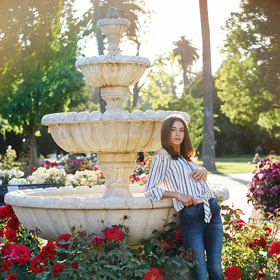 Senior girl posing by fountain and red flowers at State Capitol