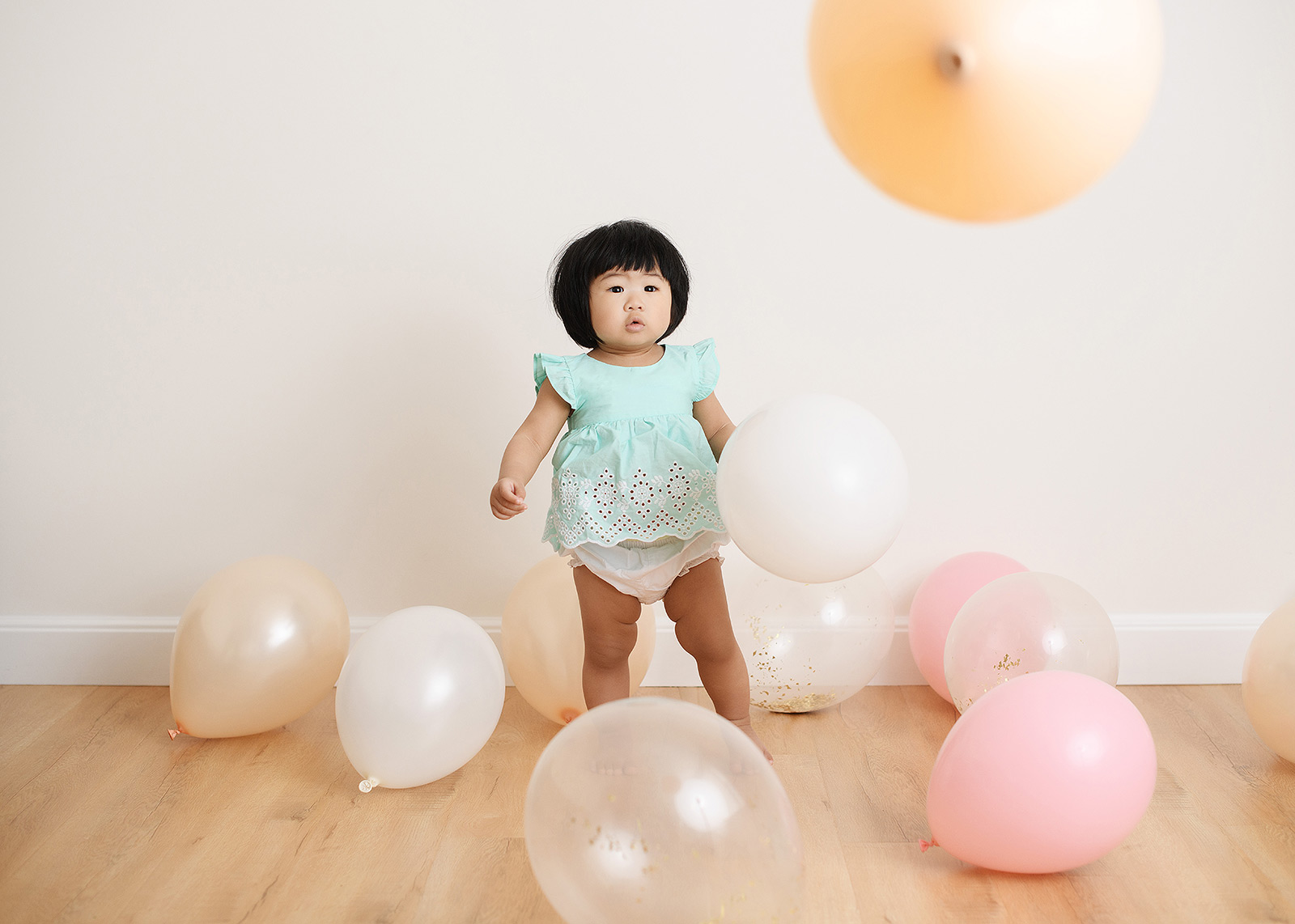 Baby girl in a sea of pastel balloons