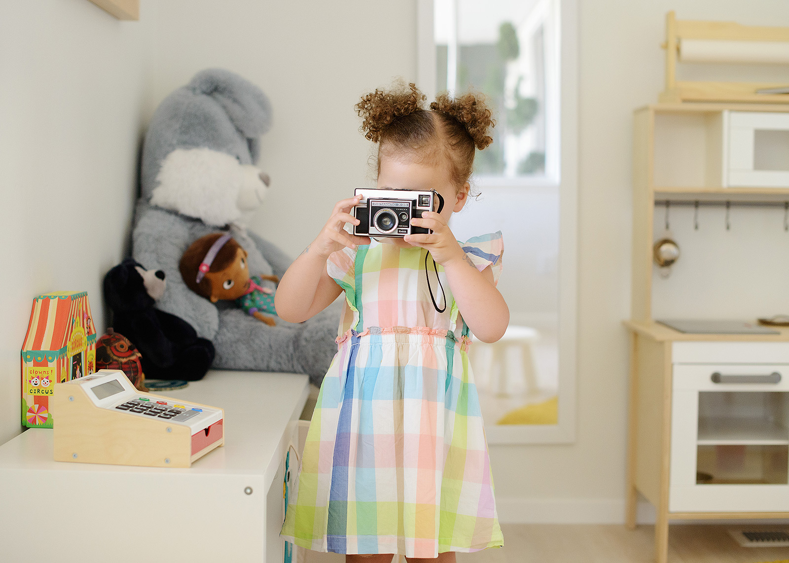 Toddler girl taking a photo in her playroom wearing plaid dress
