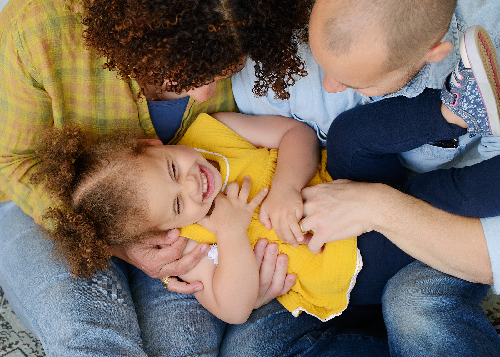 Mom and dad tickle and laugh with daughter wearing yellow