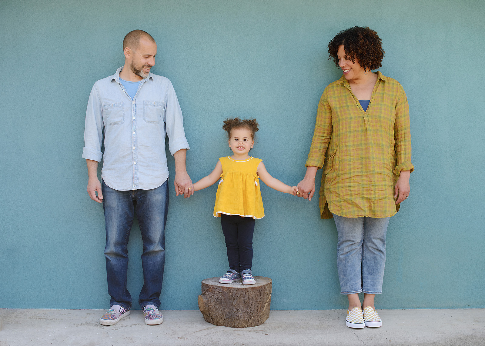 Mixed race family photo outside home with blue wall background in Sacramento