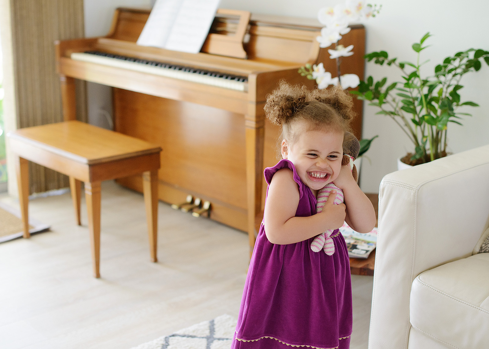 Toddler girl laughing and hugging toy with piano in background