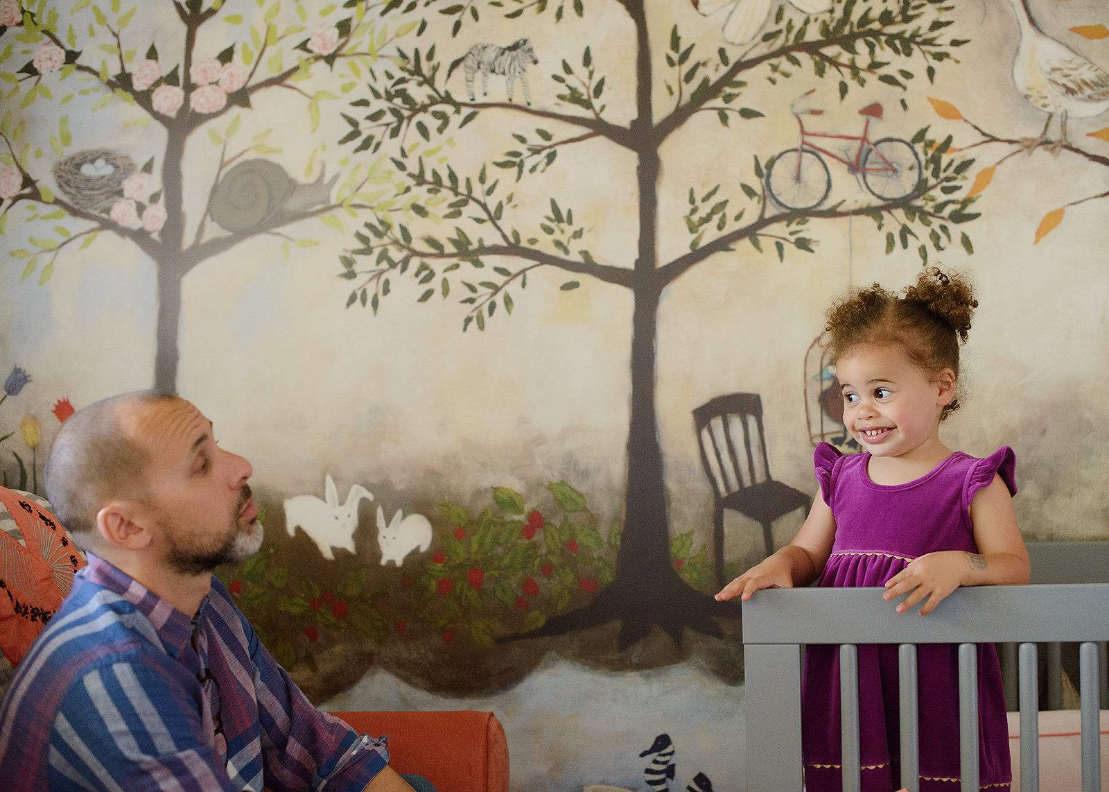 Toddler girl in nursery crib looking at dad