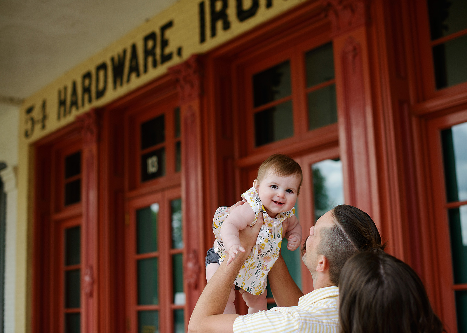 Baby girl being lifted up by dad in Old Sacramento with red door background