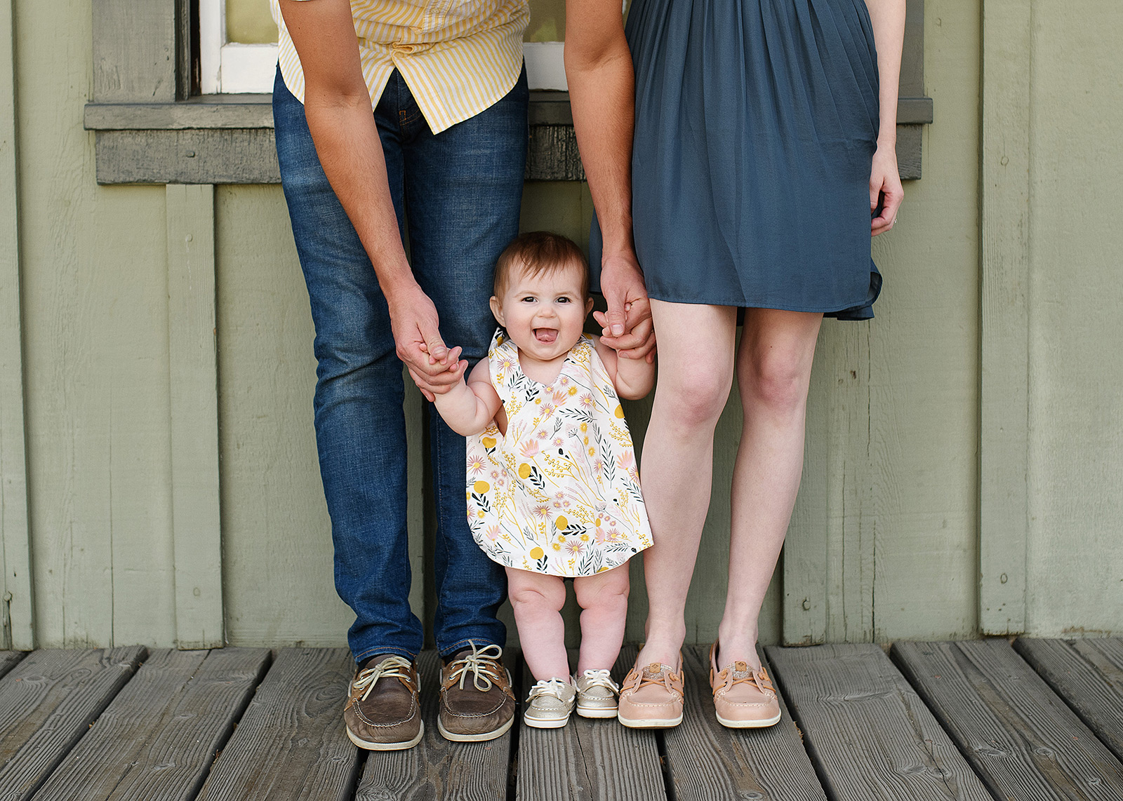 Baby girl standing up next to mom and dad wearing matching boat shoes in Old Sacramento