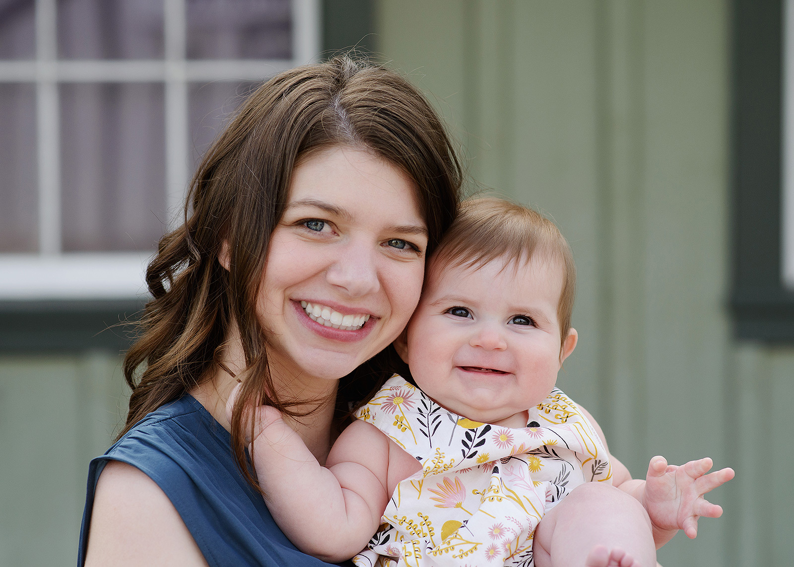 Mom and baby daughter smiling directly at camera in Old Sacramento