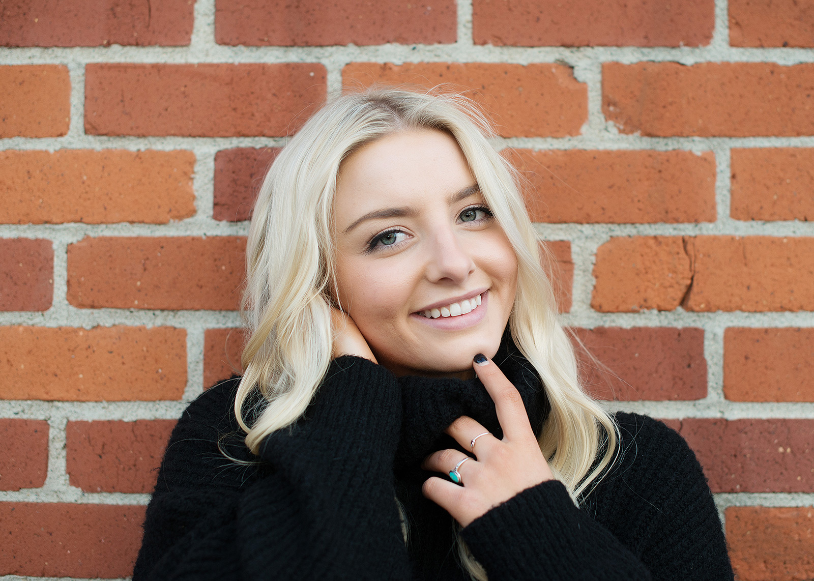 Senior portrait of teen girl smiling against brick wall background in State Capitol