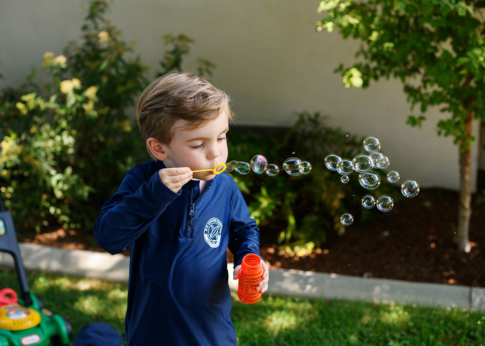 Boy blows bubbles during first birthday party outside