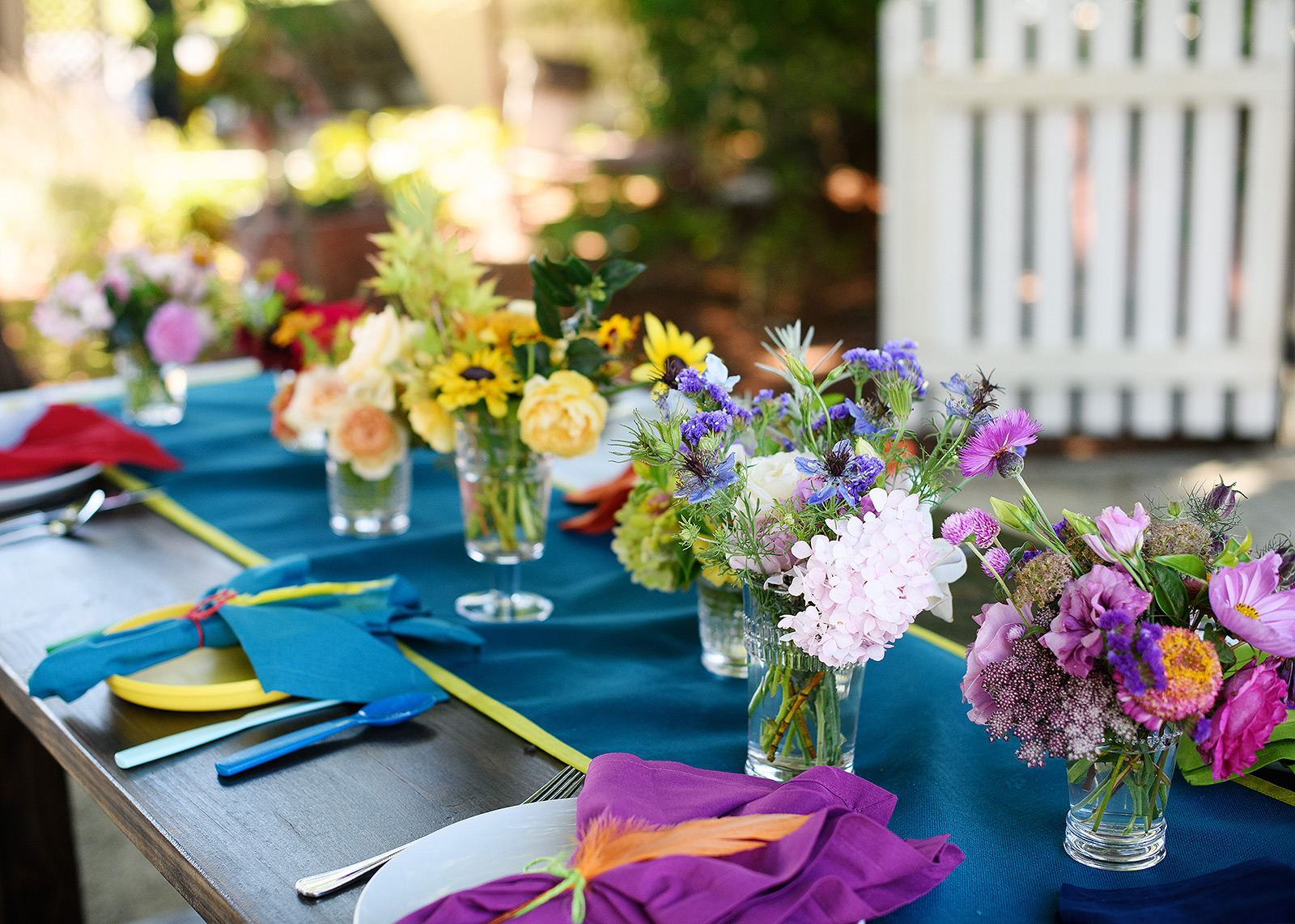 First birthday party tablescape with bright floral arrangements and napkins