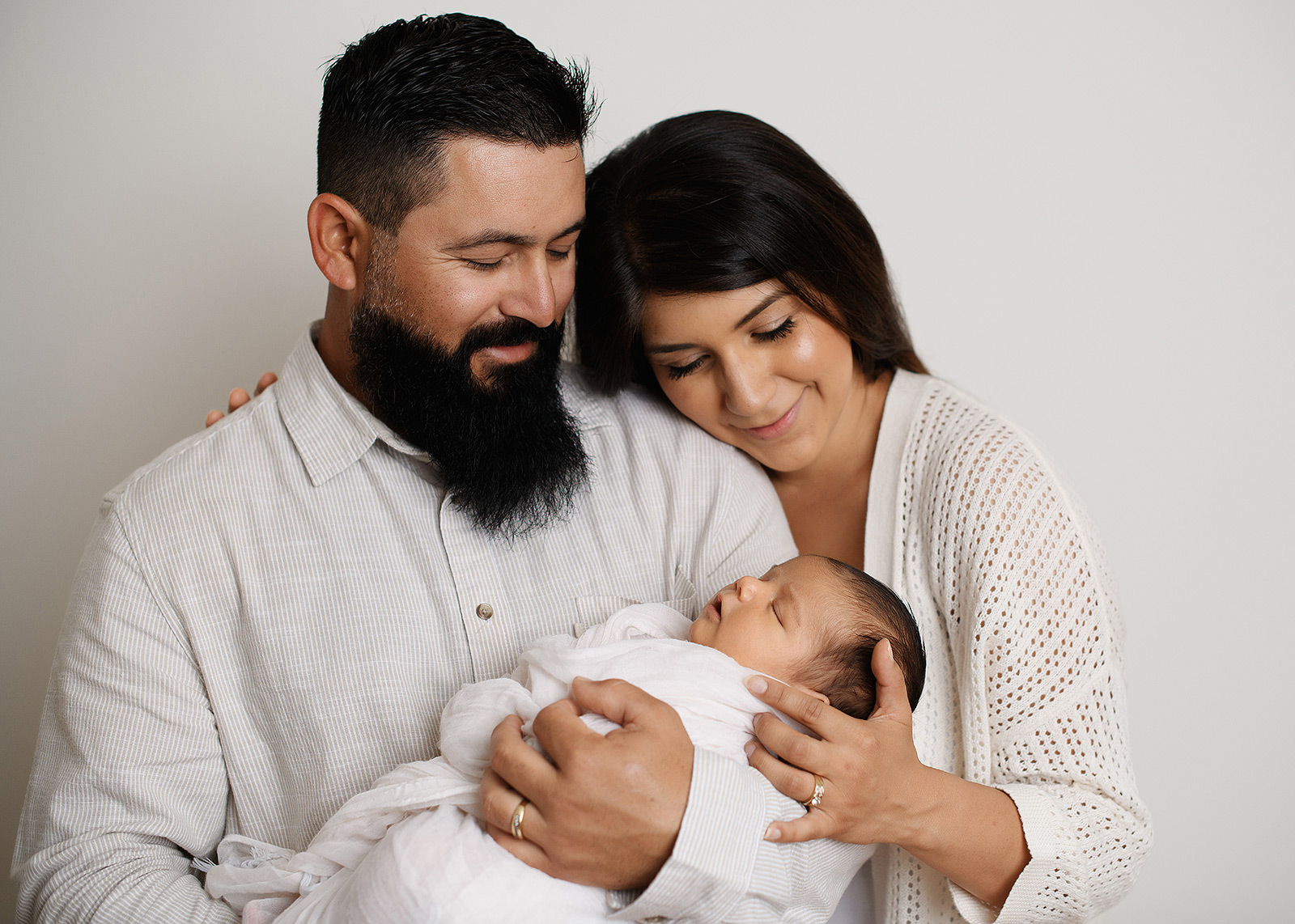 Mom and dad snuggle up to newborn baby wearing neutrals in studio