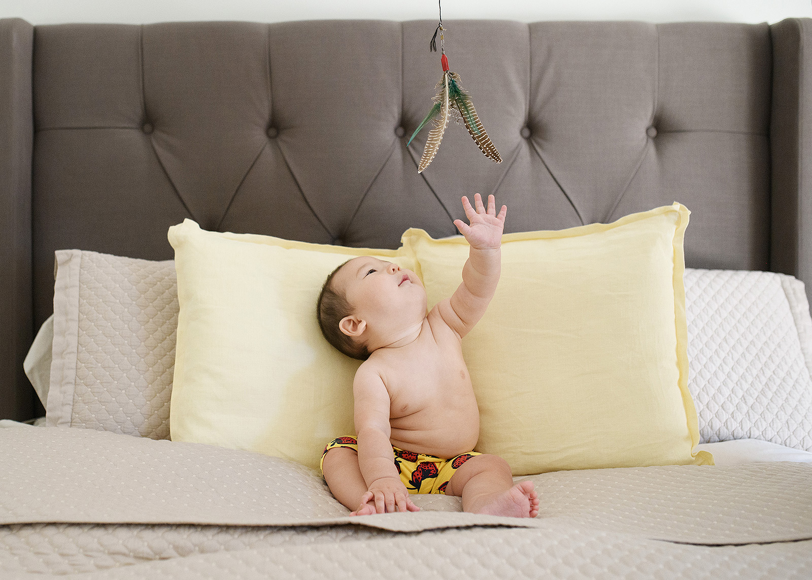 6 month baby playing with fishing lure on bed with gray headboard lifestyle session