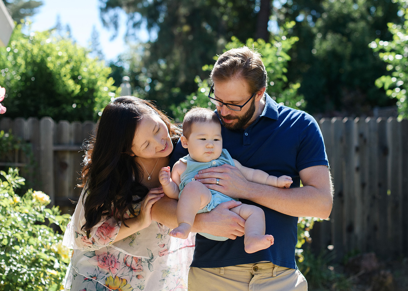 Mom and dad lovingly hold 6 month baby boy in Sacramento backyard