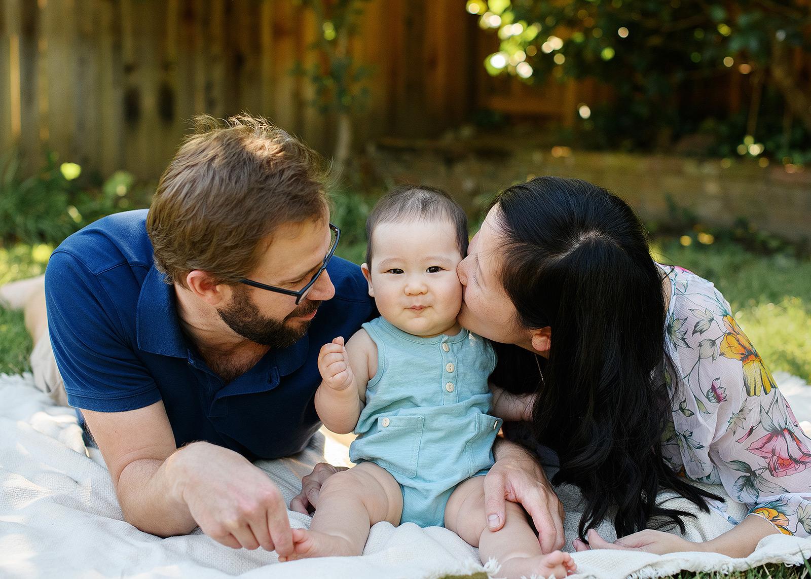 Mom kissing 6 month old baby boy on blanket in Sacramento backyard