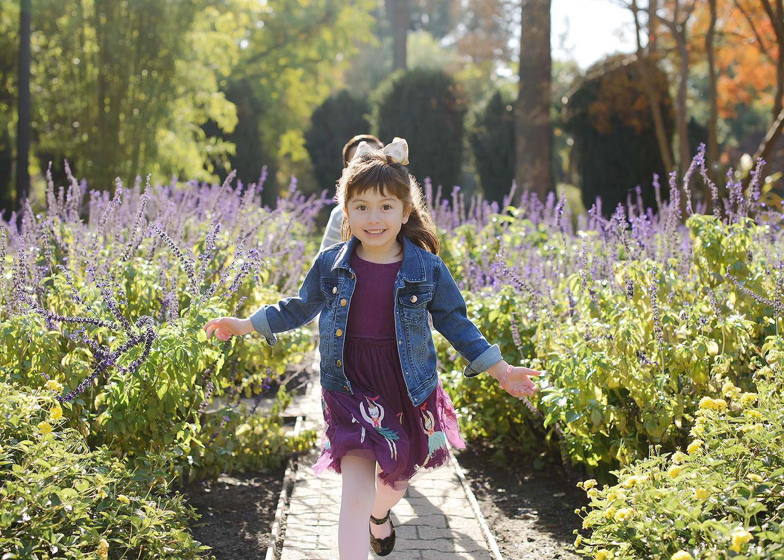 Daughter running through purple flower field wearing purple dress at State Capitol