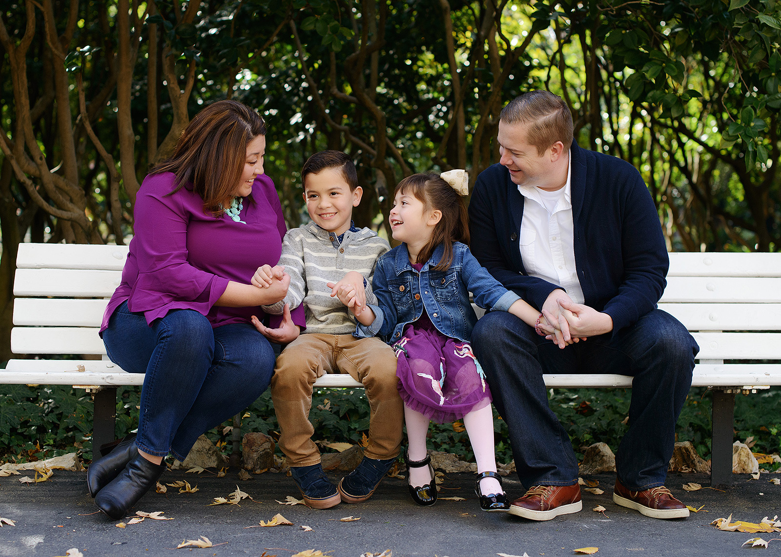Family laughing and smiling with each other sitting on bench outside of Sacramento State Capitol