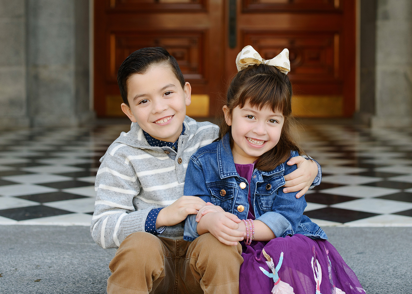 Brother and sister smiling and hugging on State Capitol steps