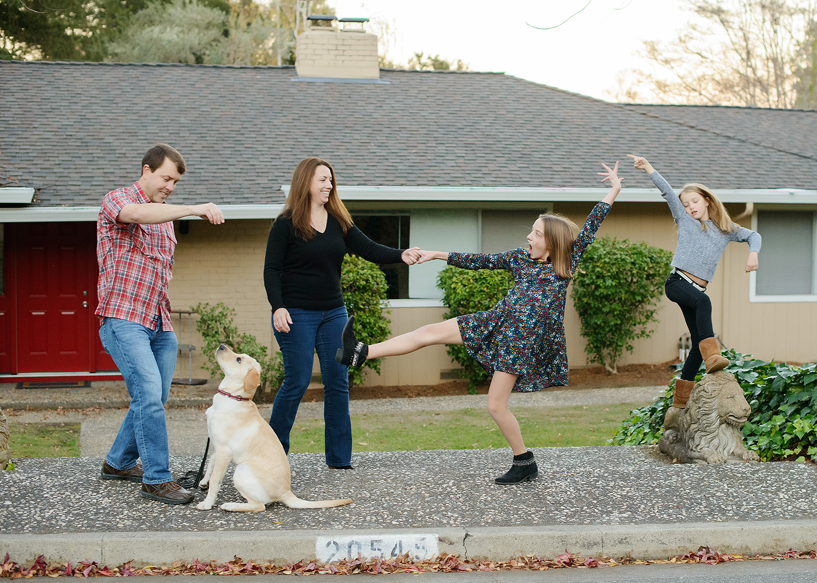 Funny family photo with daughters dancing and dad playing with dog outside of Saratoga home