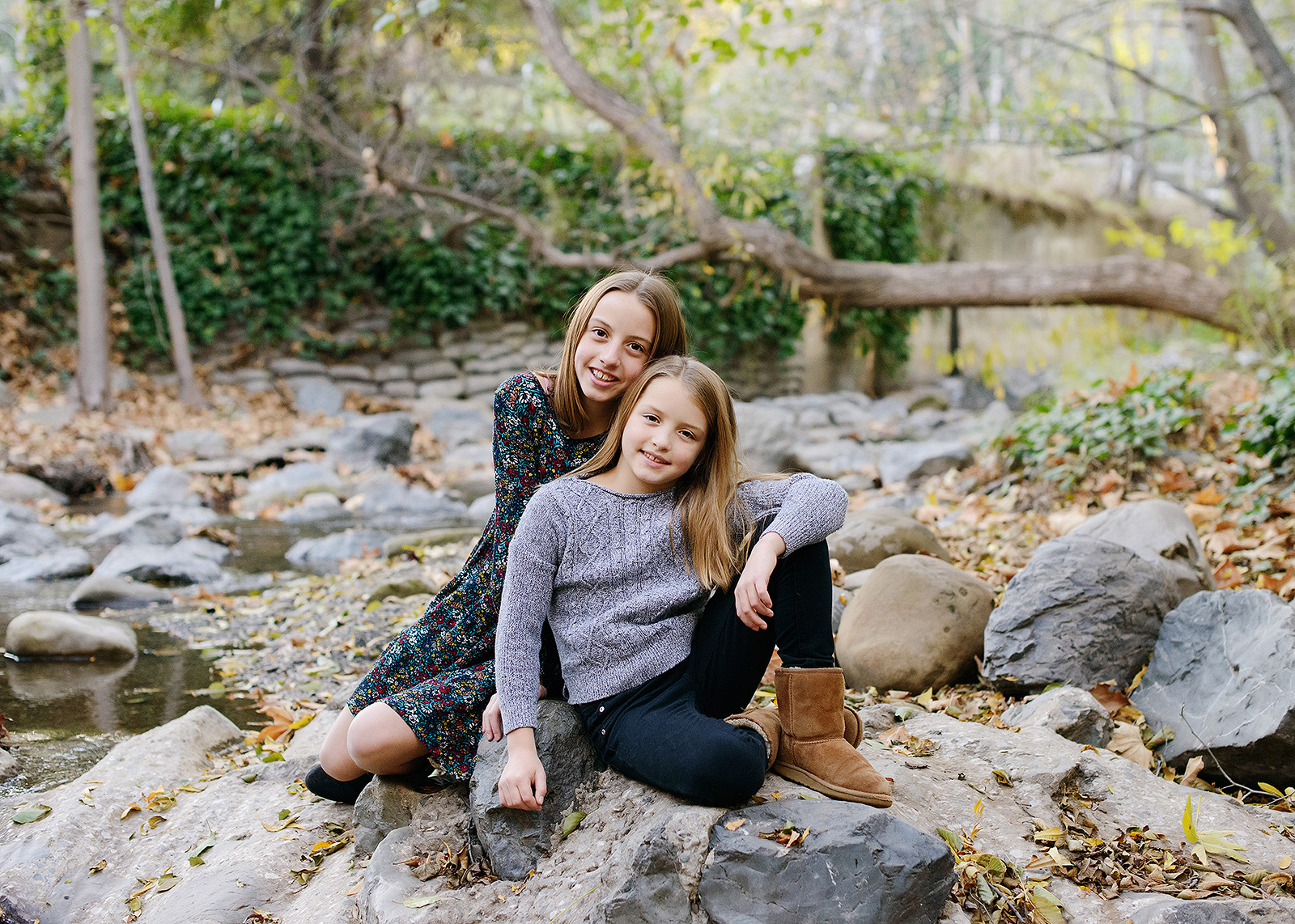 Sisters smiling for the camera on rocks in Saratoga outdoors