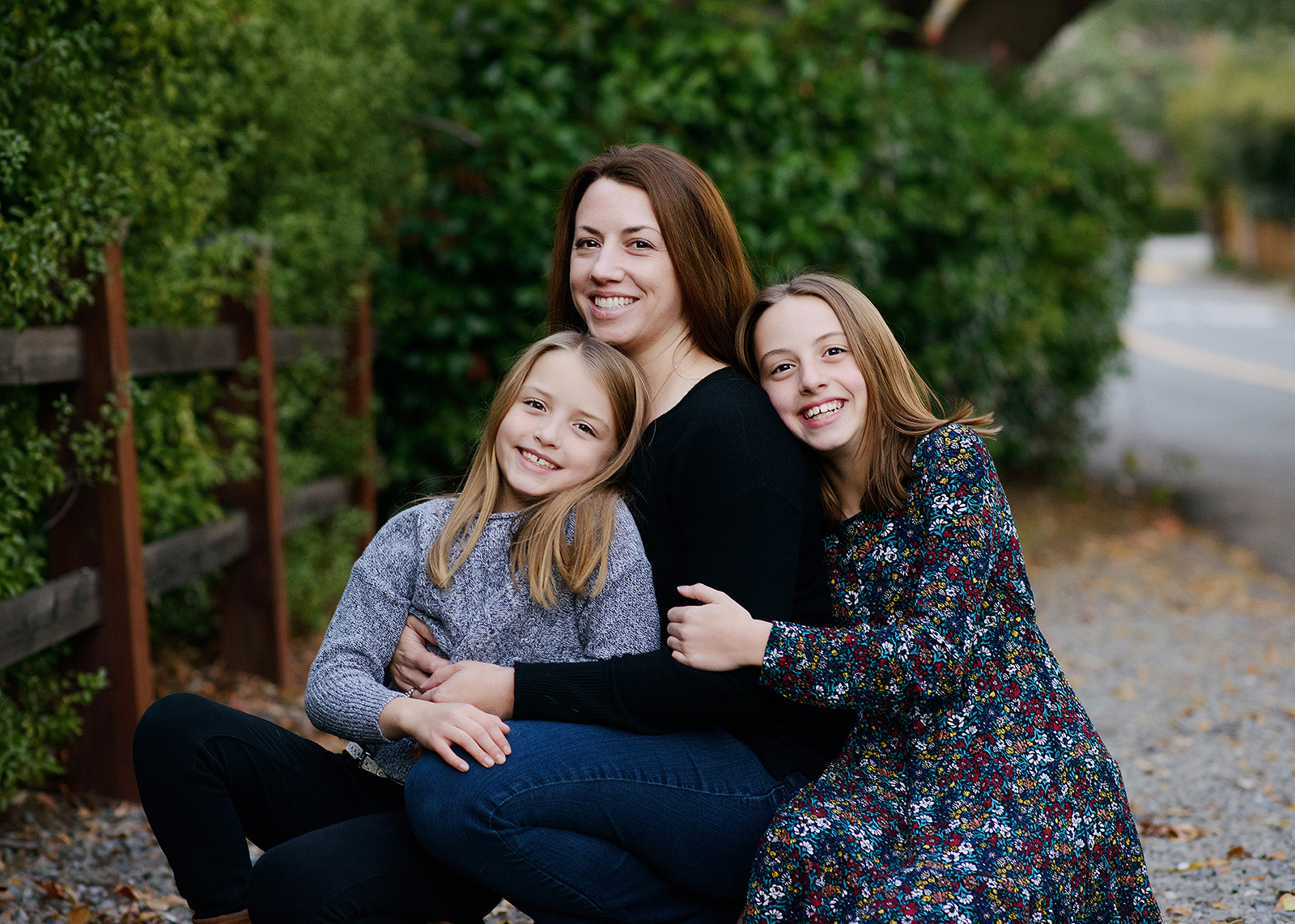 Mom and daughters hugging outdoors near trees in Saratoga